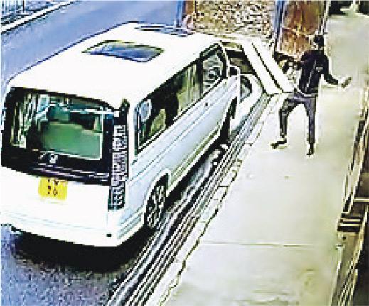 戴口罩及鴨舌帽的男子拿起一塊磚頭,扑穿車窗後,隨即掠走車內一個袋並逃去。(閉路電視截圖)