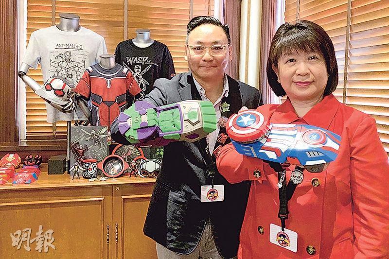 香港迪士尼樂園度假區商品總監林齊娟(右)同商品營運綜合策劃經理陳偉賢(左)示範玩最新玩具「組裝您的英雄腕甲」。(黃心悅攝)