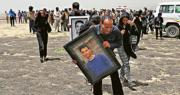 在埃塞俄比亞比紹夫圖墜機現場,大批親友昨日到場悼念罹難者。前排男子所持肖像是當日駕駛出事飛機的29歲機師格塔丘(Yared Getachew)。(路透社)