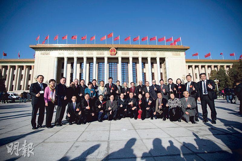 人大會議昨日在北京人民大會堂舉行閉幕會。圖為香港代表團代表在會前合影。(中新社)