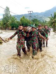 印尼軍人昨在巴布亞省東部洪災重災區之一的森塔尼(Sentani),抬出死者遺體。(法新社)