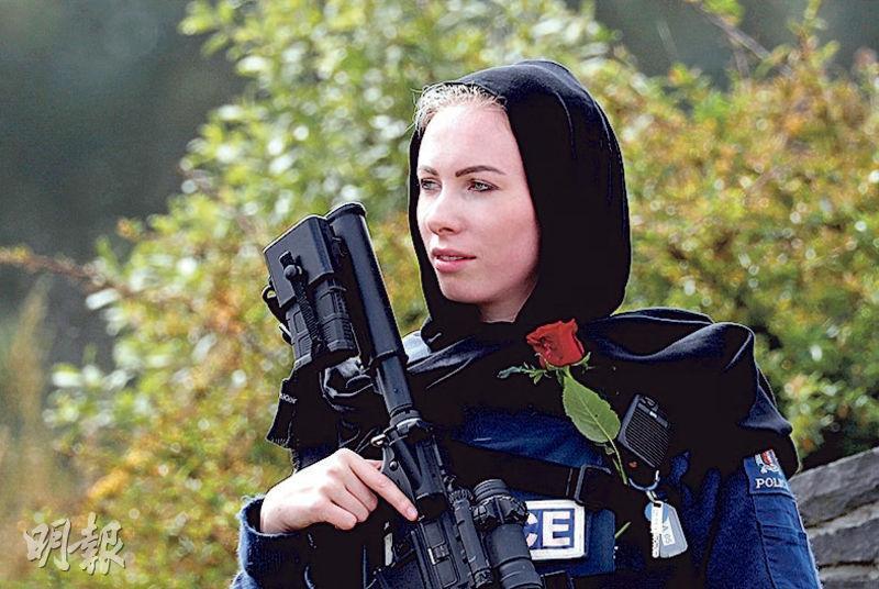 有基督城槍擊案的遇難者昨日下葬,有民眾到場悼念遇難者,其間有戴頭巾的女警持槍駐守。(路透社)