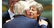 英國首相文翠珊(右)和歐盟委員會主席容克(左)周四在比利時布魯塞爾出席歐盟領袖峰會時打招呼。(路透社)