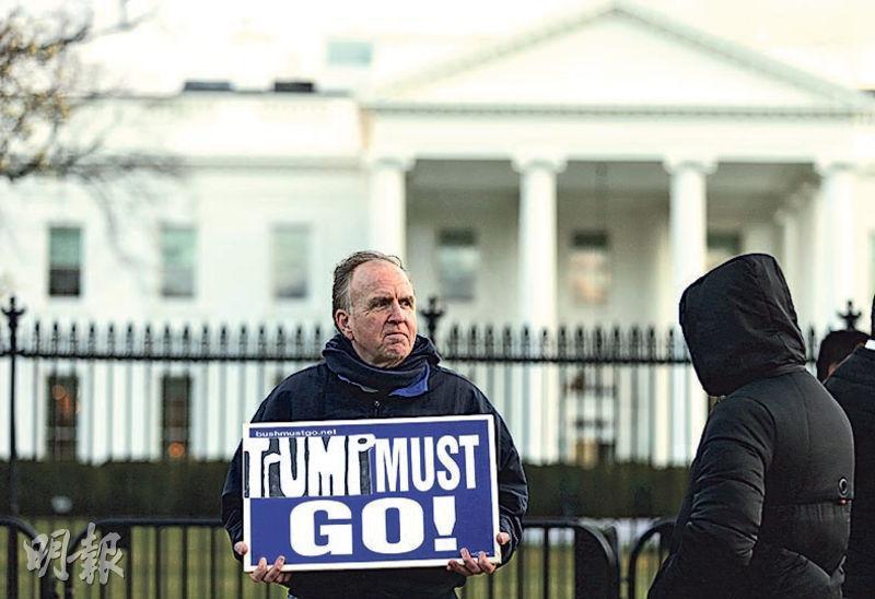 一名男子上周五在白宮外手持「特朗普必須走人」的標語牌表達訴求。(路透社)