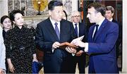 國家主席習近平(前中)周日在法國尼斯與法國總統馬克龍(右)會面時,獲贈存世僅兩本的1688年法國出版的《論語導讀》法文版原著。(新華社)