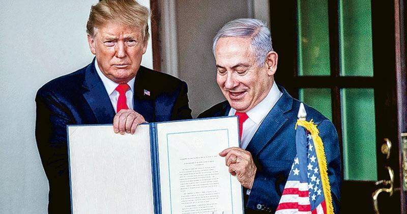 美國總統特朗普(左)和以色列總理內塔尼亞胡(右)周一在白宮展示由前者簽署、美國承認以色列對戈蘭高地擁有主權的公告。(法新社)