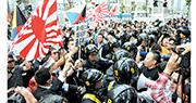 2013年5月,日本防暴警察在東京新宿區大久保,居中分隔反韓團體(左)與朝鮮裔居民及反歧視人士。(網上圖片)