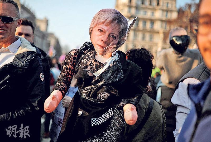有脫歐支持者上周五拿着戴上首相文翠珊面具的氣球公仔,到國會大樓外集會。(路透社)