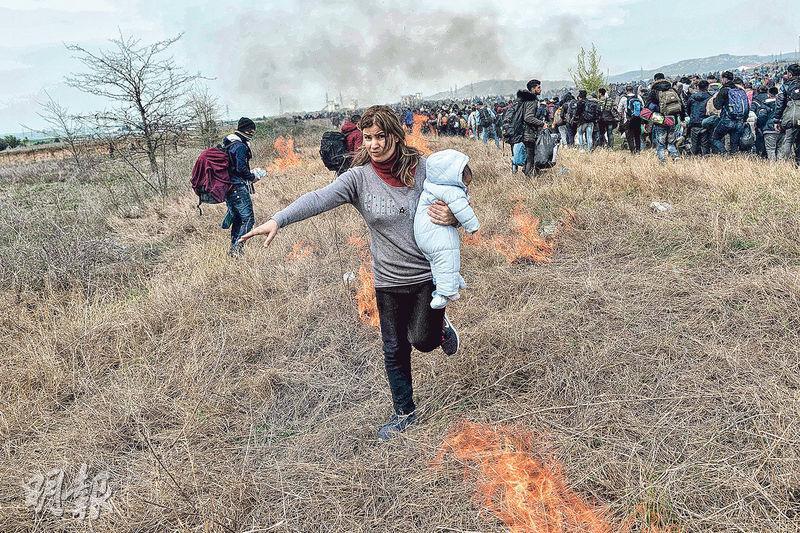 大批難民周五在邊境跟希臘防暴警察衝突,一名女子抱着嬰兒走避。(法新社)