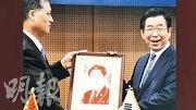 廣東省長馬興瑞(左)錯將京畿道知事李在明的肖像畫,贈給首爾市長朴元淳(右)時,朴一直保持笑容。(網上圖片)