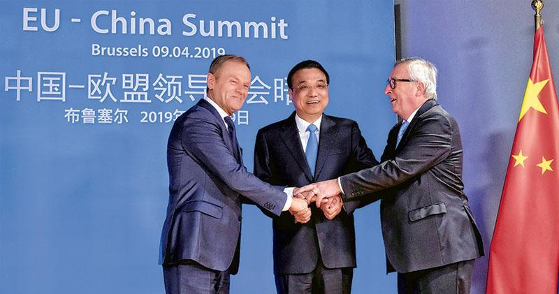 中歐峰會前,中國總理李克強(中)受到歐洲理事會主席圖斯克(左)、歐盟委員會主席容克(右)的歡迎,3人握手合影。(路透社)