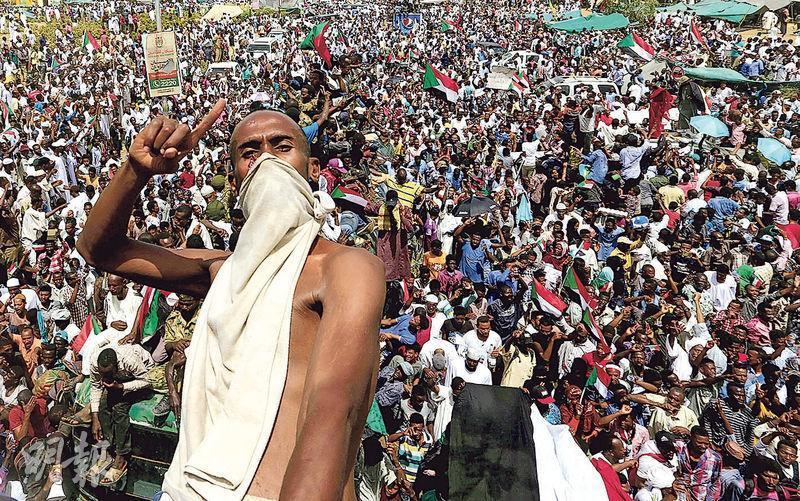 蘇丹軍方政變推翻專制總統巴希爾後設立過渡委員會掌權,惹來尋求文人政府上台的民眾不滿,繼續集會抗議。圖為一名示威者站在軍車上擺出姿勢。(路透社)