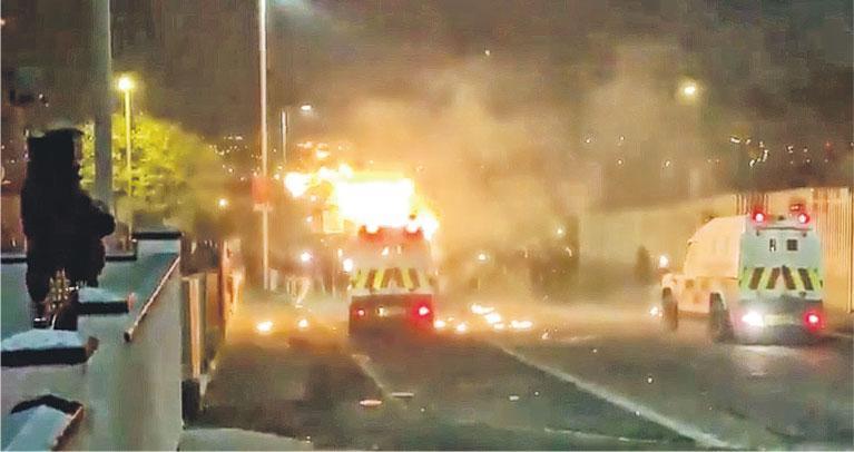 北愛爾蘭警方周四晚在倫敦德利執行搜查任務期間與民眾發生衝突,有緊急救援車輛疑遭暴徒投擲燃燒物導致起火。(路透社)