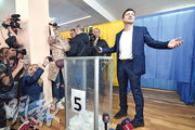 烏克蘭諧星出身的總統候選人澤連斯基(右)昨天在基輔投票。(法新社)