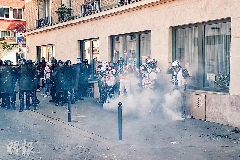 黃背心示威者上周六再度上街,是巴黎聖母院火災後首次,他們抗議馬克龍過度關心聖母院重建,漠視民眾苦况。圖為醫療人員在巴黎街頭困於警方發射的催淚氣體白霧之中。(法新社)