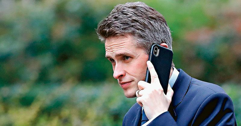 因涉嫌向傳媒泄露國安會有關華為5G設備採用的爭論,英國國防大臣韋廉信被革職。首相文翠珊聲言證據「令人信服」,但韋廉信堅持否認。圖為韋廉信今年3月底前往首相府期間在談電話。(法新社)