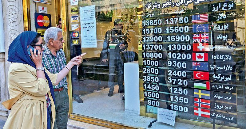 4月24日德黑蘭一間兌換店顯示伊朗里亞爾兌各主要貨幣匯價。伊朗貨幣因受美國制裁壓力而大幅貶值,直接衝擊舉國民生經濟。(法新社)
