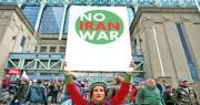在比利時布魯塞爾,一名環保人士周日以自由神像打扮參加氣候遊行,並高舉「不要伊朗戰爭」的標語。(網上圖片)