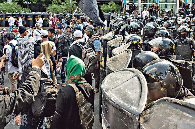 印尼首都雅加達昨日有示威者不滿大選結果,聚集到選舉監督委員會的大樓前抗議,當局派出大批警員戒備。(新華社)