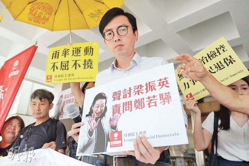 吳文遠在審訊前批評律政司今次的申請是虛耗公帑,支持者在他身後舉起黃傘。(李紹昌攝)
