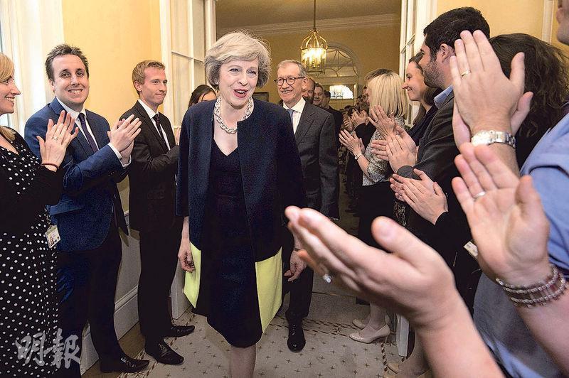文翠珊(中)2016年7月成為首相,與丈夫菲利普(後)踏入首相府時獲職員夾道歡迎。(資料圖片)