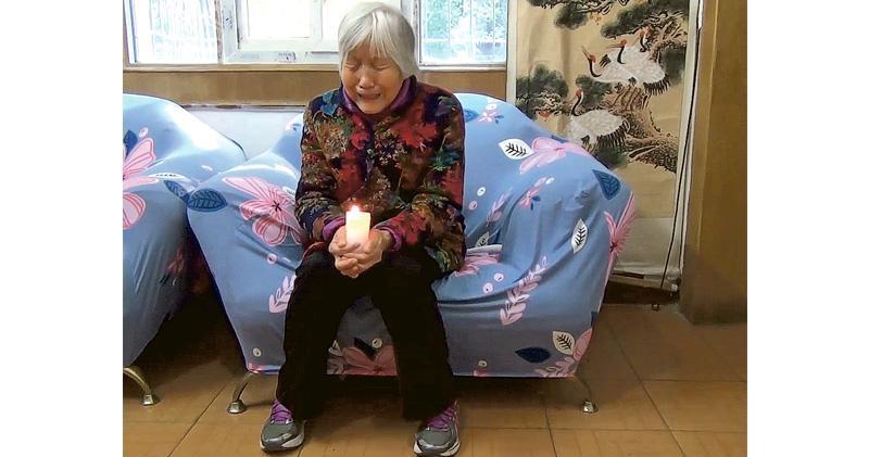 遇難學生劉洪濤的母親齊國香,在片段中手持蠟燭悼念兒子,並稱自己多年來在兒子死忌僅能在家中哭着悼念,不能有公開紀念活動,哭着祈求兒子原諒。(互聯網截圖)