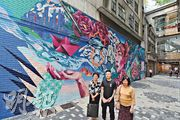 市建局今年4月起,委託日本藝術家Takamitsu Takagaito(中)美化中環鴻德大廈面向興隆街的外牆,並繪畫一幅以香港為主題、融合本地傳統及西方現代元素的巨型壁畫。該廈業主立案法團委員方秀心(左)表示,美化大廈外牆後,令人有煥然一新的感覺。圖右為該廈法團秘書姜瑞英。(李紹昌攝)