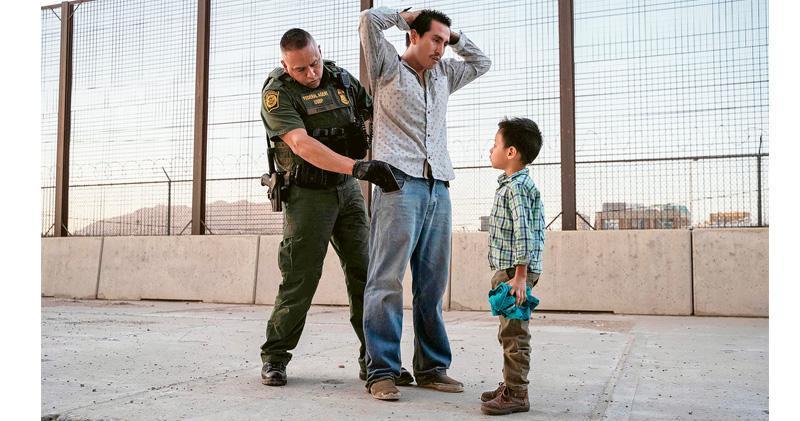 美國得州接壤墨西哥邊境的艾爾帕索市,5月中旬有邊防人員檢查一名從危地馬拉抵達當地的男子,該男子的兒子在旁邊看着搜身過程。(法新社)