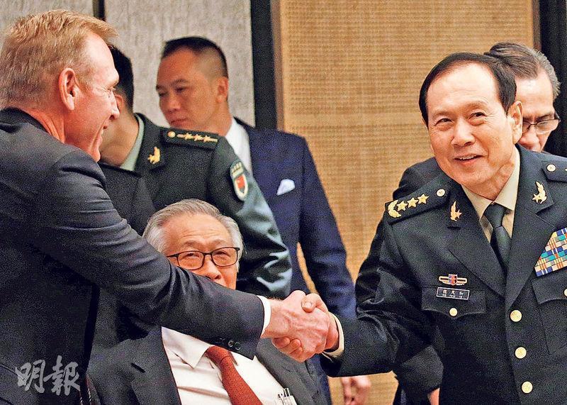 美國署理國防部長沙納漢(左)與中國國防部長魏鳳和(右),昨日在「香格里拉對話」的部長級圓桌會議上握手。(路透社)