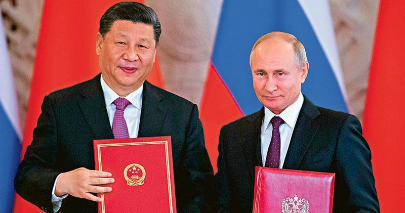 國家主席習近平昨在莫斯科與俄羅斯總統普京舉行會談,雙方同意將兩國關係提升為「新時期全面戰略協作伙伴關係」。圖為習近平和普京交換文件。(法新社)
