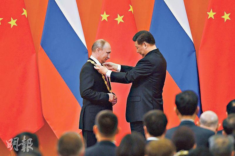 習近平提到,普京是他最好的知心朋友。去年6月普京訪華時,中方授予普京「友誼勳章」,圖為習近平(右)為普京(左)戴上勳章。(法新社)