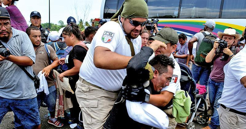 墨西哥國家移民局職員上周三(5日)在恰帕斯州一次政府聯合行動中,拘捕準備北上美國的偷渡客。(路透社)
