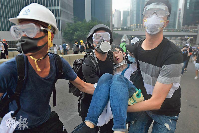 警方昨午在金鐘不斷發射催淚彈驅散示威者,眾人四散走避,有年輕女示威者不適暈倒,由其他示威者合力抬走找尋救援。(鍾林枝攝)