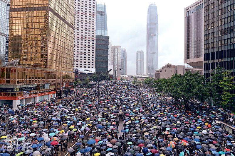 留守了一夜後,反對修訂《逃犯條例》示威者昨早佔領金鐘夏愨道,至中午一度下雨,眾人一起舉傘,場面猶如2014年的雨傘運動。(鍾林枝攝)