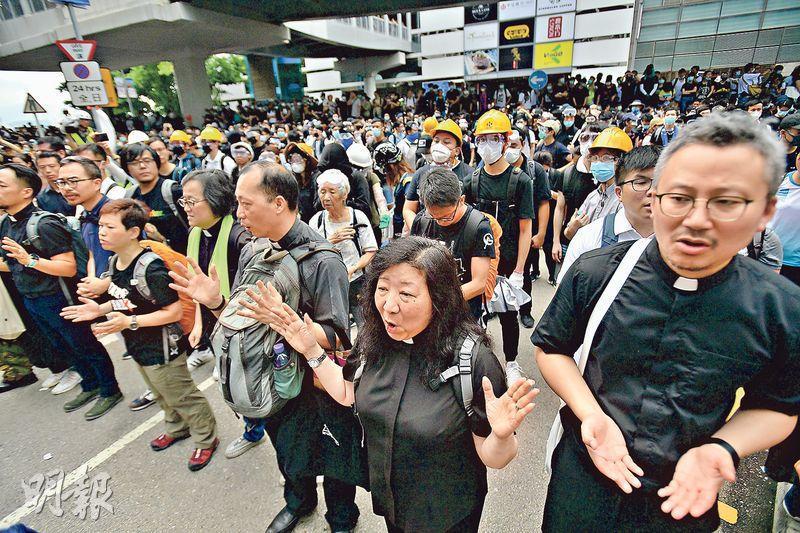 基督教協進會指出,從不同教會代表得悉有不少教牧人員及神職人員到了示威現場,圖為昨有宗教團體站在示威者與警方防線間唱詩禱告。(楊柏賢攝)