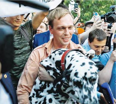俄羅斯記者戈盧諾夫(中)周二獲撤藏毒罪,大批支持者在莫斯科的刑事調查辦公室外慶祝他重獲自由。(路透社)