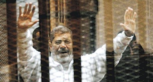 圖為穆爾西在審訊期間於犯人欄內雙手示意。(網上圖片)