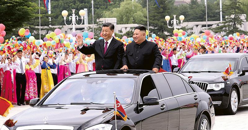 習近平昨天抵達朝鮮展開為期兩天的國事訪問,平壤市內約25萬人夾道歡迎,前往錦繡山太陽宮廣場途上,他與朝鮮領袖金正恩在車上向群眾揮手。(新華社)