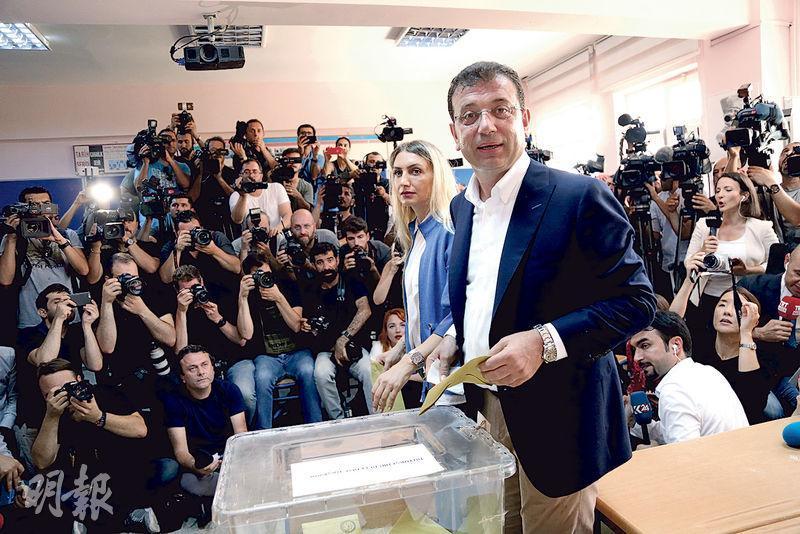 伊斯坦布爾市長重選昨日舉行,反對派候選人伊馬姆奧盧(前)跟妻子和兒子一同到票站投票。(路透社)