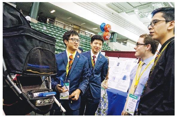 裘錦秋中學(元朗)中四生蕭兆廷(左一)、鄧皓徽(左二)向評審介紹「智能安全嬰兒車」。(青協提供)