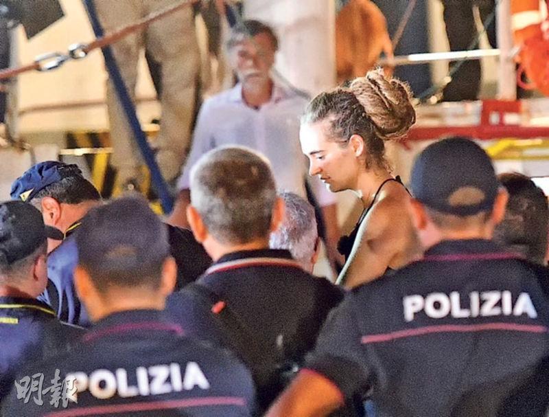 地中海救援船「海洋-監察3」號的女船長拉克特(右)周六凌晨由意大利警員押走。她憂慮42名船民的安危而強行把船泊岸,被讚是反抗民粹意大利政府的英雌。(路透社)
