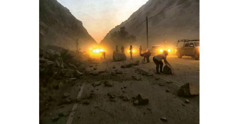 上周五7.1級地震引發加州克恩縣山泥傾瀉,令一段高速公路受阻,途經駕駛者要落車協助清理泥石為自己解圍脫困。(路透社)