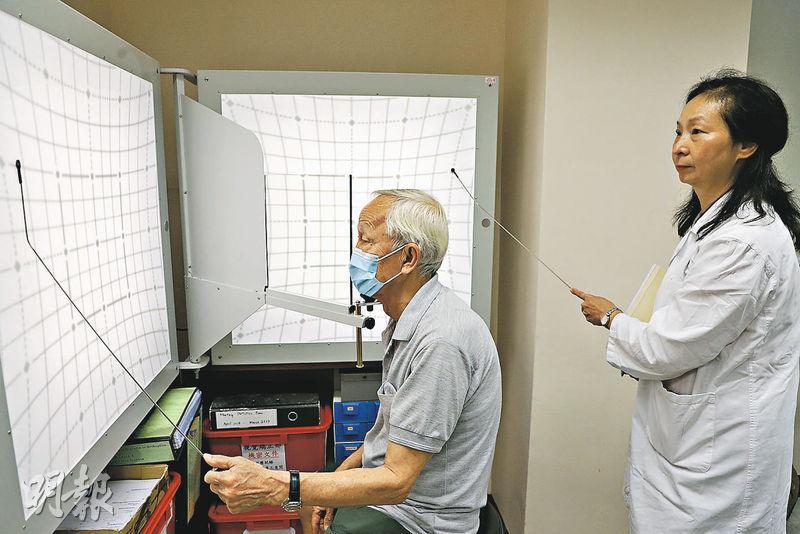 現年74歲的黃先生(左),數年前曾中風,去年底出現重影(複視)問題,他今年到香港眼科醫院求診,獲轉介做視覺矯正治療,圖中的赫氏表(Hess chart)可檢查患者複視嚴重程度,圖右為香港眼科醫院視覺矯正師趙惠玲。(林靄怡攝)。