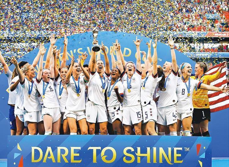 美國女子足球國家隊周日在法國里昂擊敗荷蘭,第四度奪得女足世界盃,一眾隊員上台領獎時士氣高昂。前排右四為隊長韋冰露。(新華社)