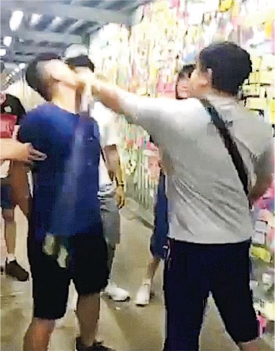 身穿藍衣的麥先生昨凌晨在牛頭角連儂牆外被中年男子連打多拳,但未有還手。中年男子當場被捕,被控兩項「襲擊致造成實際身體傷害」罪,下周五提堂。(網上片段截圖)