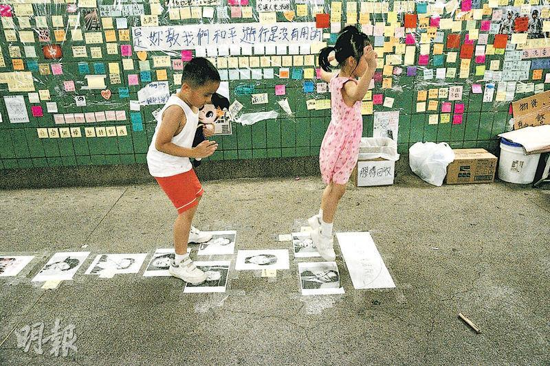大埔「連儂隧道」除市民貼紙表達意見,更有人將官員相片貼在地上,有小孩在相片上「跳飛機」。(黃詩雅攝)