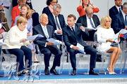 德國總理默克爾(前排左起)、葡萄牙總統雷貝洛德索薩和法國總統馬克龍,昨日在法國國慶日巡遊活動中交談。(路透社)