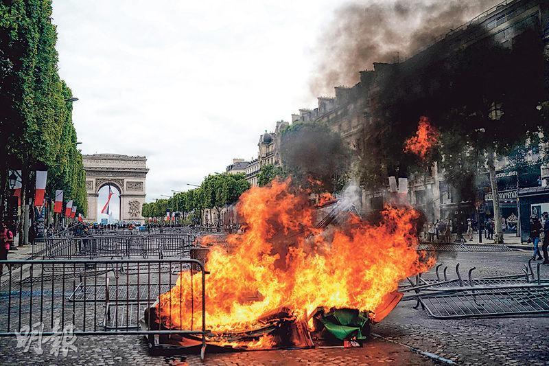 黃背心運動示威者昨日在巴黎凱旋門一帶示威,地上有燃燒的雜物。(法新社)