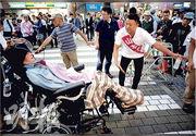 患有「漸凍人症」的船後靖彥(前)7月12日與山本太郎(右)在東京出席競選活動。(路透社)