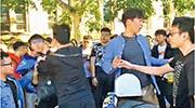 香港留學生在澳洲布里斯班的昆士蘭大學校園內,以海報解說近日本港反修訂《逃犯條例》示威活動及設連儂牆,其間被人包圍。圖中左方身穿黑衣、說普通話的男子,與戴眼鏡的香港學生發生推撞,雙手伸向對方的頸。(受訪者提供)